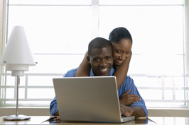 Smiling male and female couple with laptop