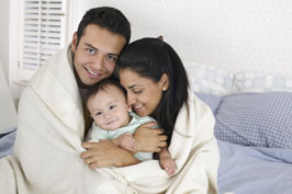 Smiling family - male, female and baby wrapped in blanket sitting on bed